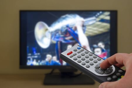 Photo pour Football match winner team celebrating with the cup in television, with a remote control in the hand - image libre de droit
