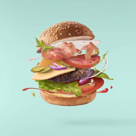 Photo pour Delicious burger with flying ingredients isolated on turquoise background - image libre de droit