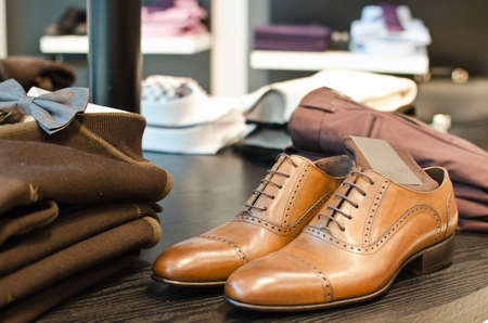 Shoes, shirts and other clothes in a men fashion store.