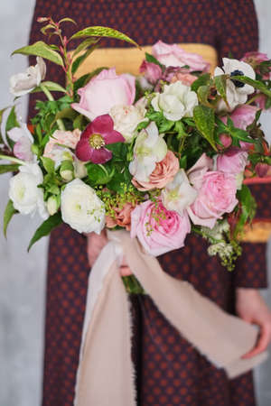 Foto de Young female florist holding a freshly made blooming floral bouquet of pastel carnations and eucalyptus against a gray wall. - Imagen libre de derechos
