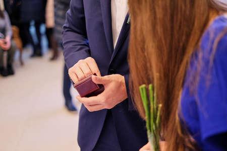 Foto de A man in a blue suit holds a small wooden gift box of wedding rings. wedding gift - Imagen libre de derechos