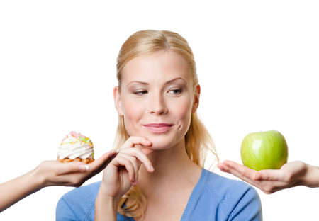 Foto de Beautiful woman makes a tough choice between cake and apple, isolated on white - Imagen libre de derechos
