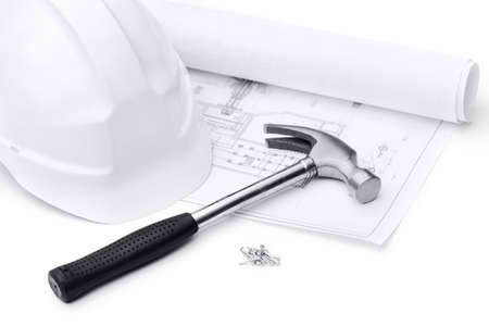 White hard hat, hammer on the druft and nails, isolated on white