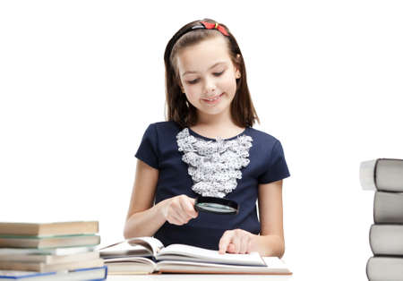Little schoolgirl wonders about interesting details in the book, isolated, white background