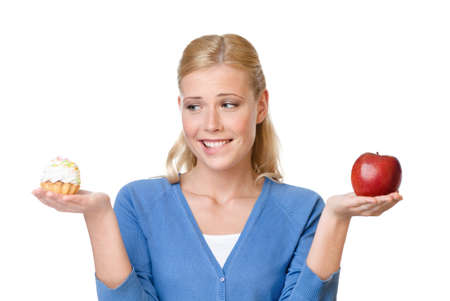Attractive woman makes a tough choice between cake and apple, isolated