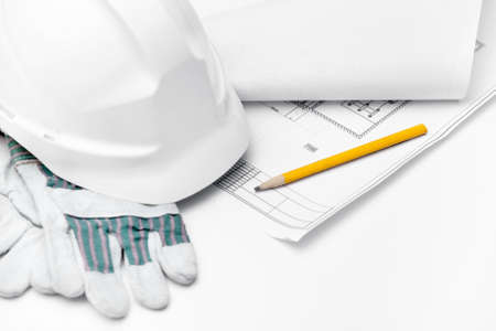 White hard hat on the gloves and pencil on the druft, isolated on white background