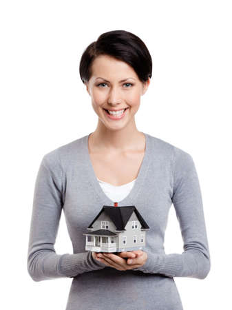 Young woman hands small toy house in front of herself, isolated on white
