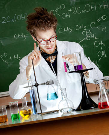 Mad professor gestures forefinger while conducting an experiment in his laboratory