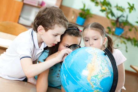 Three friends examine a school terrestrial globe