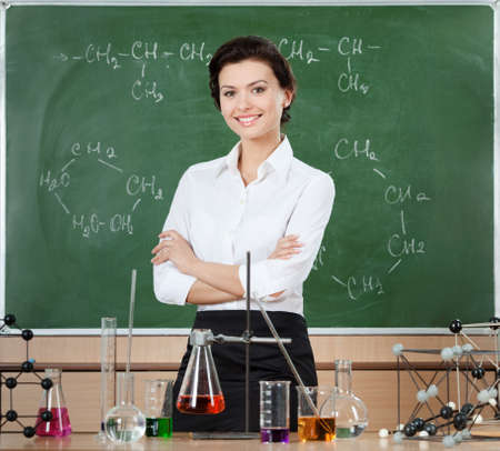 Smiley chemistry teacher surrounded with chemical glassware stands near the chalkboard