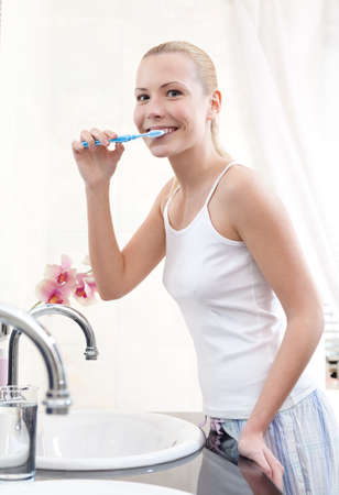 Beautiful woman brushes her teeth in bathroom