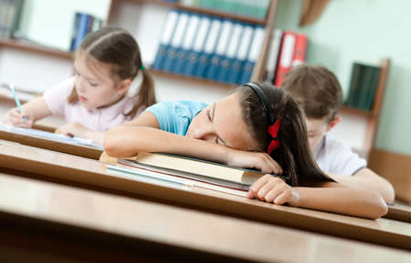 Tired schoolgirl sleeps at the desk