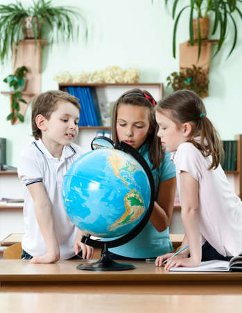 Friends stare at school globe and try to find something with magnifying glass