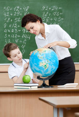 Geography teacher shows something to the pupil at the terrestrial globe