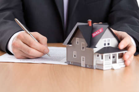 Real estate concept - businessman signs contract behind house architectural model