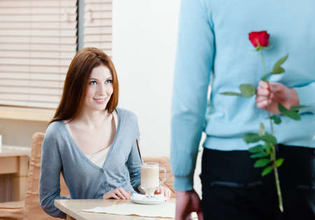 Man keeps crimson rose behind his back to present it to his girlfriend