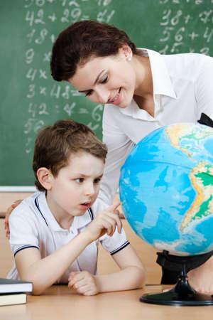Little schoolboy is looking for something at the terrestrial globe