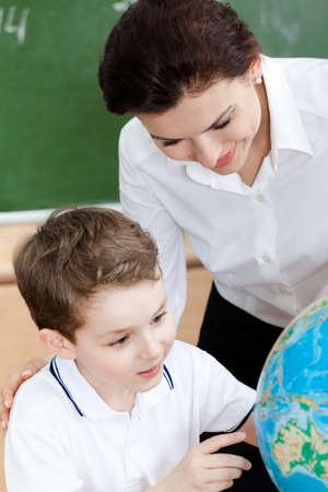 Little schoolboy studies geography with teacher