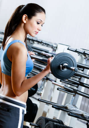 Woman with dumbbells in sport centre