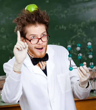 Mad scientist with a green apple on his head shows forefinger while handing molecularmodel