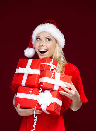 Woman in Christmas cap holds a set of presents, isolated on purple