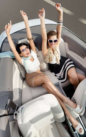 Photo pour Top view of happy women in sunglasses with their hands up sit in the cabriolet - image libre de droit