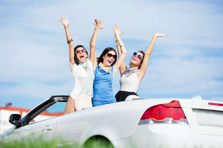 Photo pour Group of girls stands in the automobile with hands up. Happy journey of joyful teenagers - image libre de droit