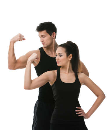 Two sportive people in black sportswear showing their biceps, isolated on white background