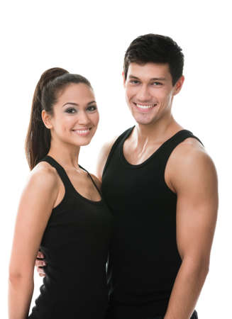 Two sportive people in black sportswear embrace each other, isolated on white