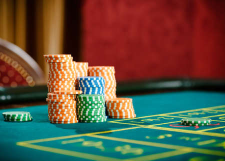 Close up of piles of chips on the roulette table. Symbol of addiction to the gambling