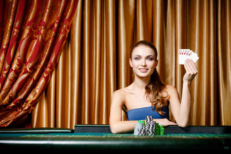 Portrait of the female gambler at the poker table handing cards