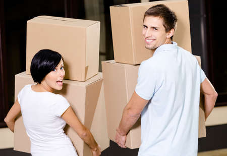 Back view of happy couple carrying pasteboard packages while moving to new house