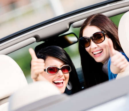 Photo pour Two happy girls sitting in the car and thumbing up turn back and have fun while having little car trip - image libre de droit
