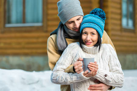 Half-length portrait of embracing couple drinking tea outdoors during winter vacations