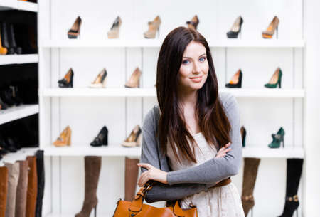 Portrait of woman in shopping center in the section of female pumps. Concept of consumerism and stylish purchase