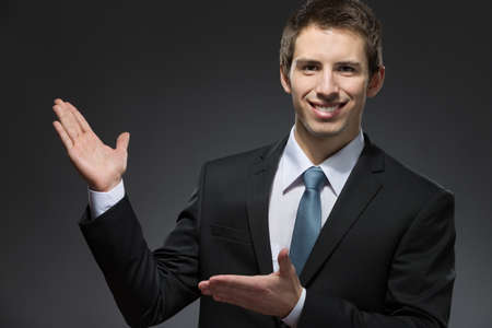 Half-length portrait of business man pointing at something with hands
