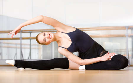 Bending female ballet dancer stretches herself on the floor in the classroom