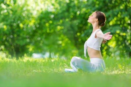 Photo pour Profile of woman sitting in lotus position with outstretched arms. Concept of healthy lifestyle and relaxation - image libre de droit