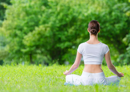 Backview of woman who sits in lotus position zen gesturing. Concept of healthy lifestyle and relaxation