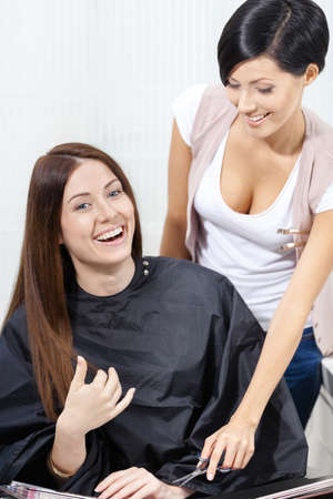 Half-length portrait of hair stylist talking to the client sitting on the chair. Concept of stylish haircut and fashion
