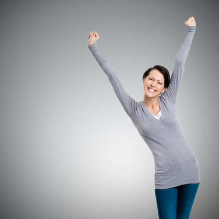 Beautiful girl gesturing triumphal fists, isolated on grey background
