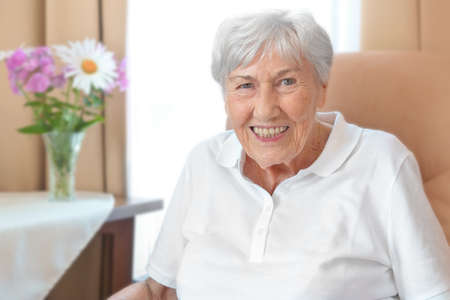 Photo pour Smiling senior woman with an osteoporosis stoop in a comfy chair in her room at a retirement home. - image libre de droit