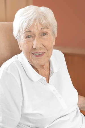 Photo pour Cheerfully smiling senior woman in a comfy chair in her room at a retirement home. - image libre de droit
