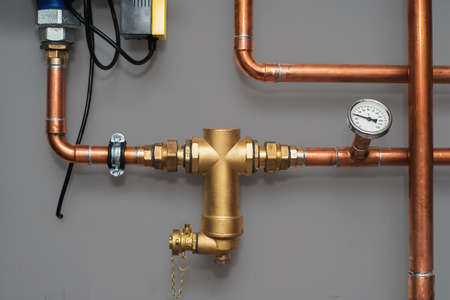 Photo pour Thermometer and water filter for central heating system on a grey wall in a boiler room. Close up. - image libre de droit