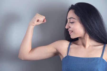 Photo pour happy young woman showing her muscles - image libre de droit