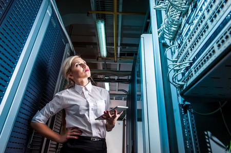 Photo pour Young engineer businesswoman in network server room. Russia. - image libre de droit