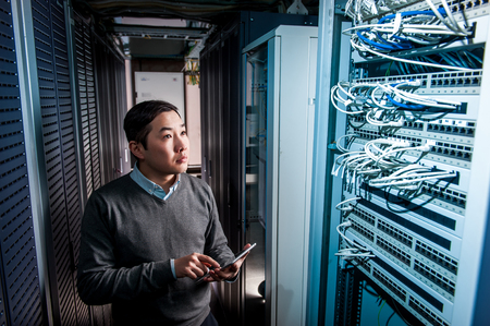 Photo pour Young engineer businessman in network server room - image libre de droit