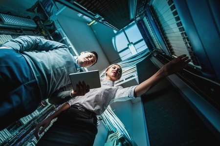 Photo pour Young engineers businessmen in network server room - image libre de droit