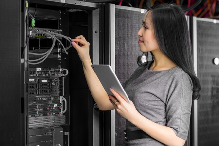 Photo pour Young engineer businesswoman with tablet in network server room - image libre de droit