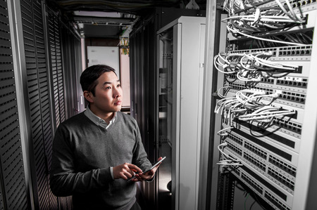 Photo pour Young engineer businessman in network server room - image libre de droit